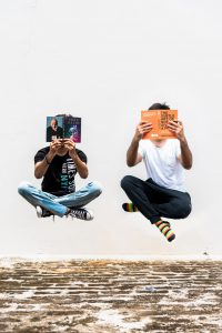 two people floating in the air while reading